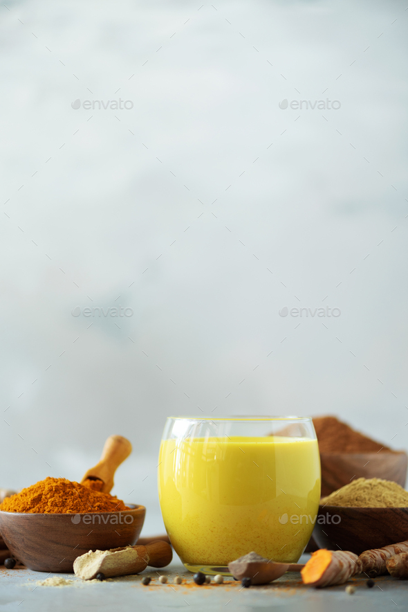 Ingredients for turmeric latte. Turmeric powder, curcuma root, cinnamon, ginger over grey background - Stock Photo - Images