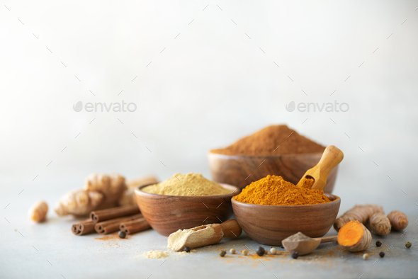 Ingredients for turmeric latte. Ground turmeric, curcuma root, cinnamon, ginger, black pepper on - Stock Photo - Images