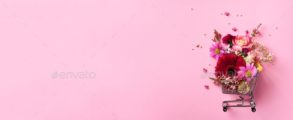 Shopping trolley with flowers on pink punchy pastel background. Banner with copy space. Top view - Stock Photo - Images