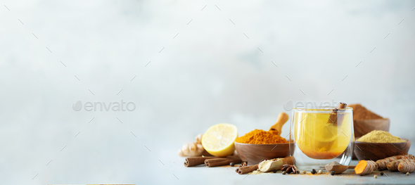 Ingredients for turmeric hot tea on grey background. Healthy ayurvedic drink with lemon, ginger - Stock Photo - Images
