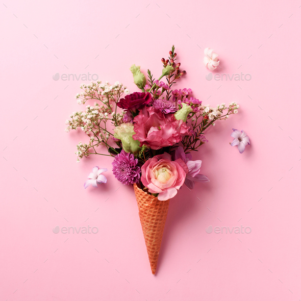 Summer minimal concept. Ice cream cone with pink flowers and leaves on punchy pastel background - Stock Photo - Images