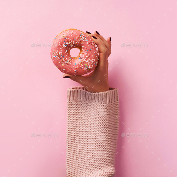 Female hands holding donut over pink background. Top view, flat lay. Sweet, dessert, diet concept - Stock Photo - Images