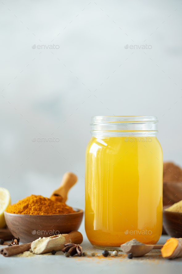 Ingredients for orange turmeric drink on grey concrete background. Lemon water with ginger, curcuma - Stock Photo - Images