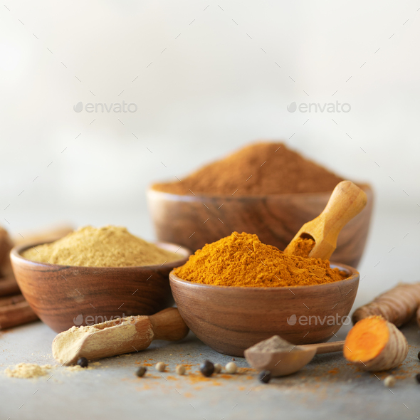 Ingredients for turmeric latte. Ground turmeric, curcuma root, cinnamon, ginger, black pepper on - Stock Photo - Images