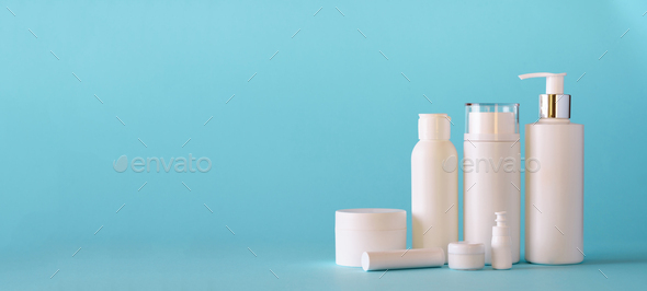 White cosmetic tubes on blue background with copy space. Skin care, body treatment, beauty concept - Stock Photo - Images