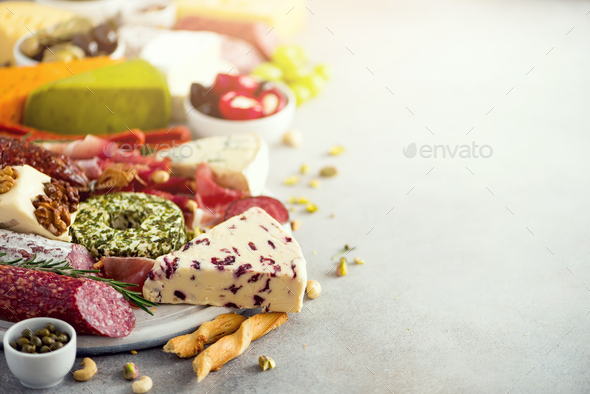 Traditional italian antipasto, cutting board with salami, cold smoked meat, prosciutto, ham, cheeses - Stock Photo - Images