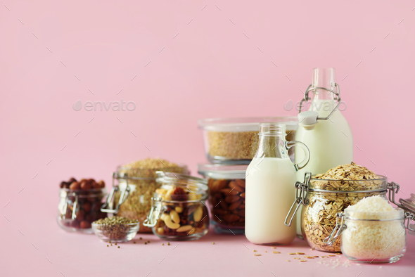 Vegan substitute dairy milk. Glass bottles with non-dairy milk and ingredients over pink background - Stock Photo - Images