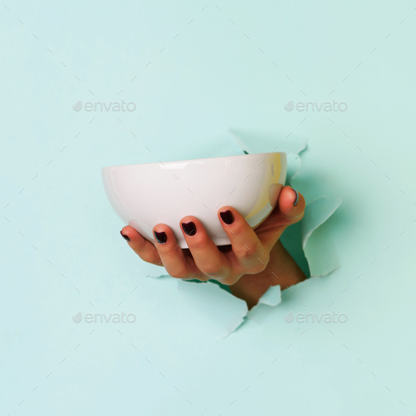 Female hand holding empty bowl on blue background with copy space. Healthy eating, dieting concept - Stock Photo - Images