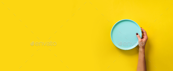 Female hand holding empty blue plate on yellow background with copy space. Healthy eating, dieting - Stock Photo - Images