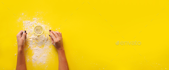 Female hand holding sieve flour on yellow background. Baking and cooking concept. Banner with copy - Stock Photo - Images