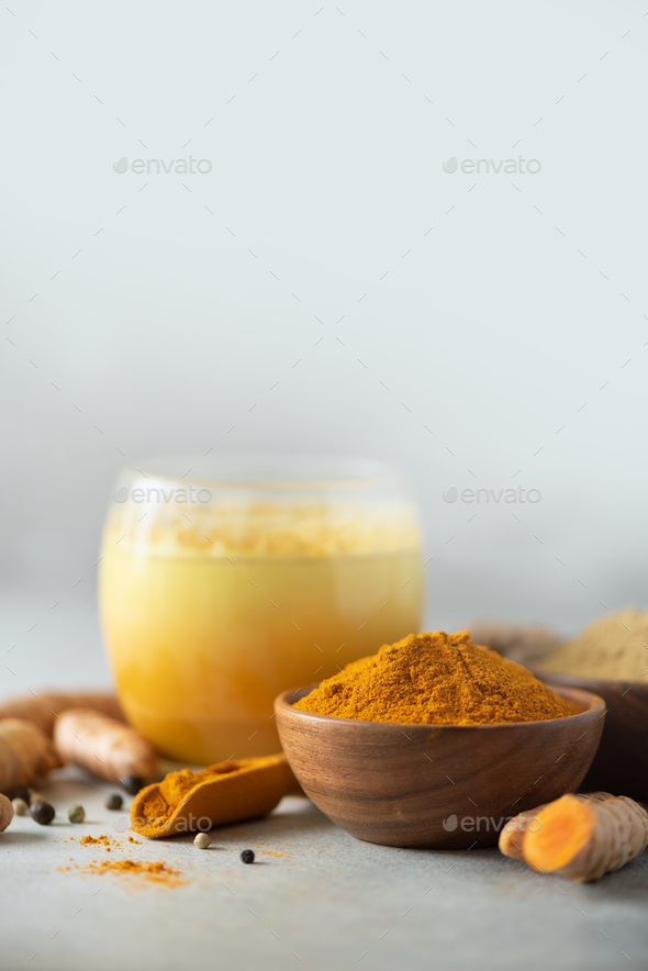 Yellow turmeric latte drink. Golden milk with cinnamon, turmeric, ginger over grey background. Copy - Stock Photo - Images