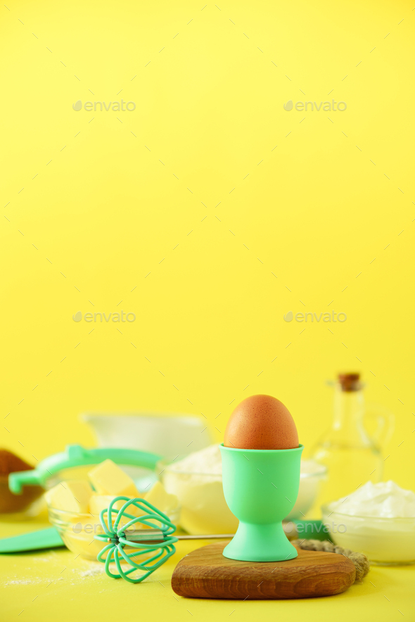 Healthy baking ingredients - butter, sugar, flour, eggs, oil, spoon, brush, whisk, milk over yellow - Stock Photo - Images
