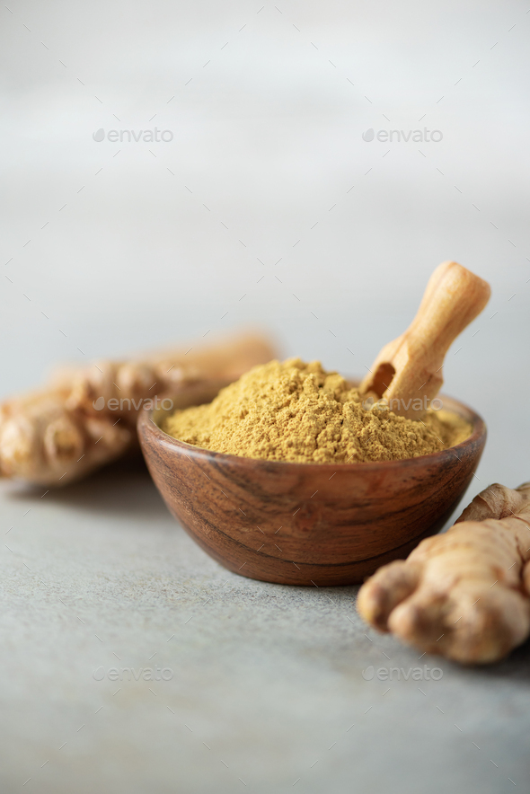 Ginger root and ginger powder in wooden bowl over grey concrete background with copy space. Immune - Stock Photo - Images