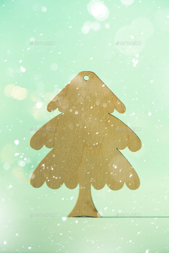 Greeting card in minimal style. Wooden Christmas tree on blue background with copy space, lights - Stock Photo - Images