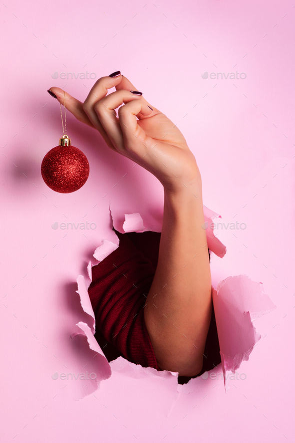 Woman holding red glittering Christmas ball in hand over pink background with snow, light bokeh - Stock Photo - Images