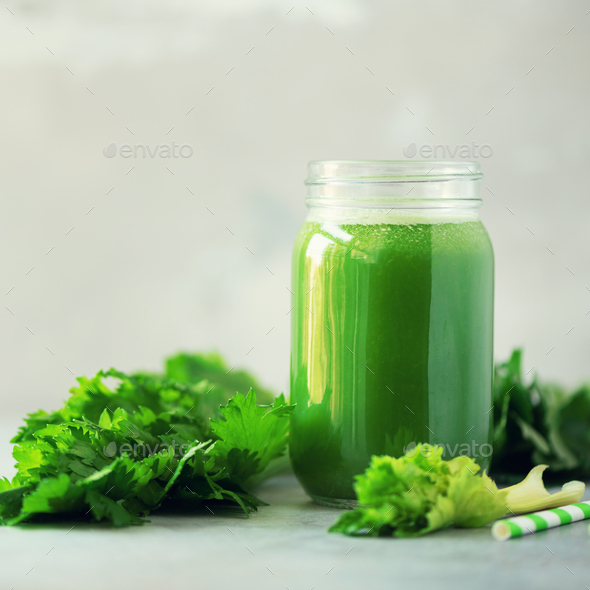 Bottle of green celery smoothie on grey concrete background with copy space. Square crop. Fresh - Stock Photo - Images