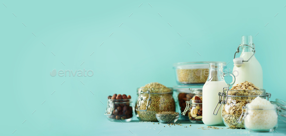 Glass bottles of vegan plant milk and almonds, nuts, coconut, hemp seed milk on blue background - Stock Photo - Images