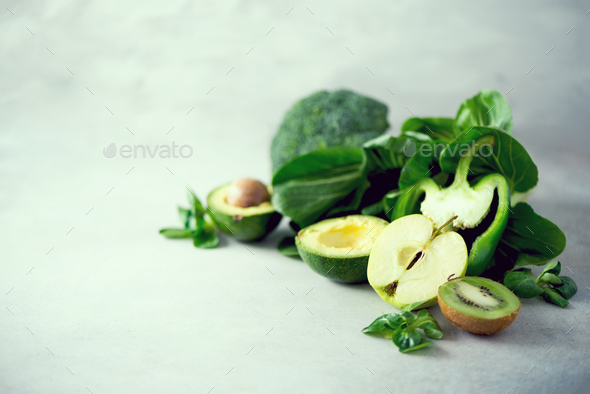 Organic green vegetables and fruits on grey background. Copy space. Green apple, lettuce, cucumber - Stock Photo - Images