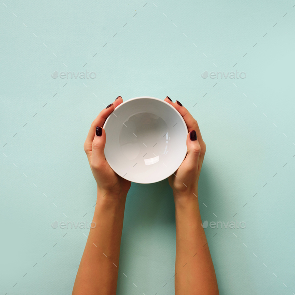 Female hand holding white empty bowl on blue background with copy space. Healthy eating, dieting - Stock Photo - Images