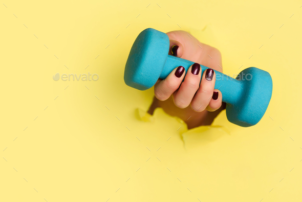 Woman hand holding blue dumbbell on yellow background. Fitness, sport, healthy lifestyle, diet - Stock Photo - Images