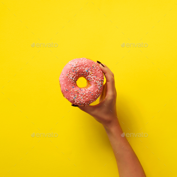 Woman hand holding delicious pink donut on yellow color background. Top view banner with copy space - Stock Photo - Images