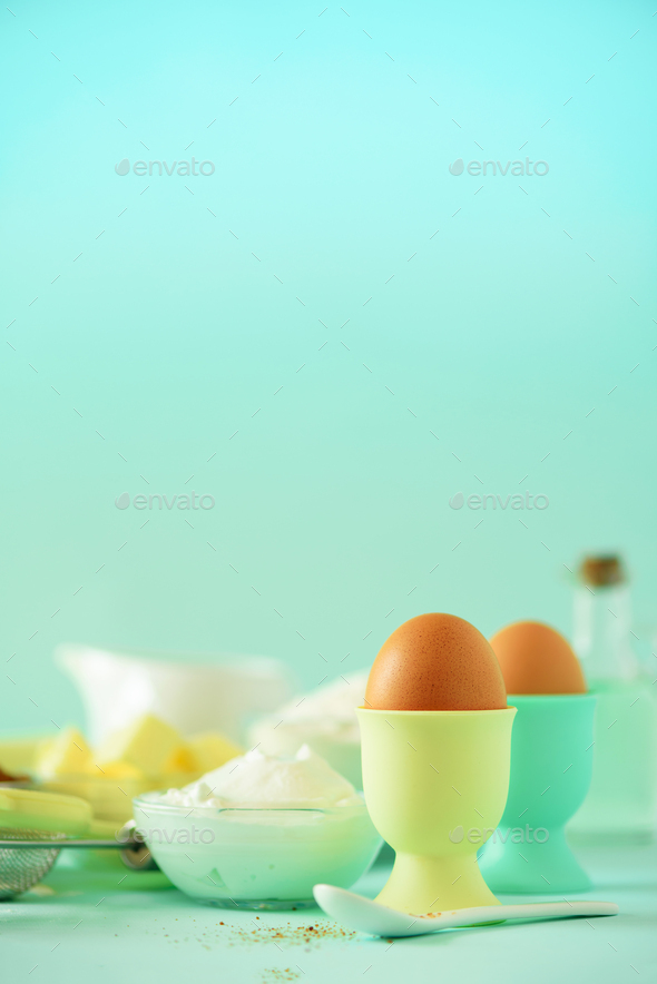 Healthy baking ingredients - butter, sugar, flour, eggs, oil, spoon, brush, whisk, milk over blue - Stock Photo - Images
