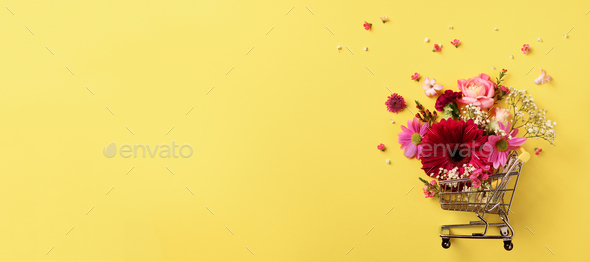 Shopping trolley with flowers on yellow punchy pastel background. Banner with copy space. Top view - Stock Photo - Images