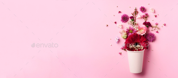 Creative layout made of white paper cup with pink flowers. Flat lay, top view. Banner with copy - Stock Photo - Images