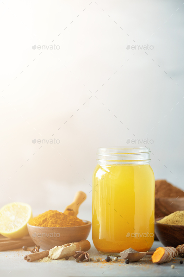 Spicy healthy turmeric drink with lemon, ginger, black pepper on grey background. Vegan hot drink - Stock Photo - Images