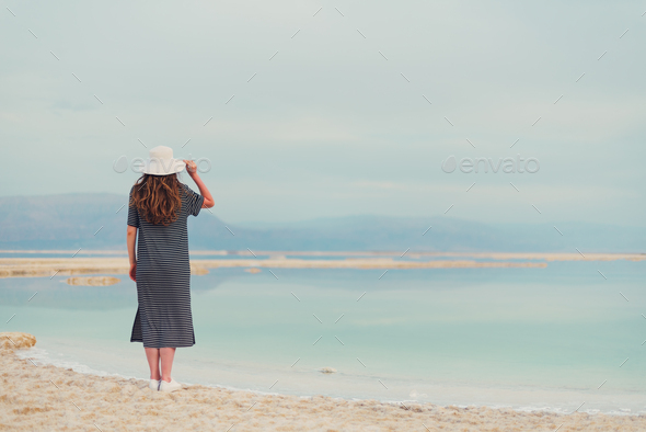 Young girl with shining blonde hair goes to seaside, Dead Sea beach. Travel, summer vacation - Stock Photo - Images