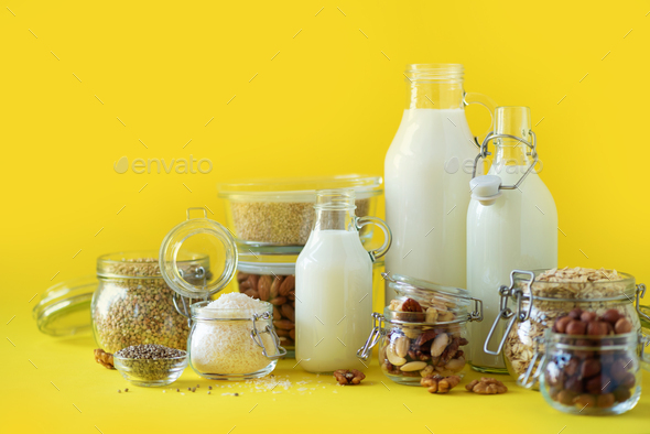 Glass bottles of vegan plant milk and almonds, nuts, coconut, hemp seed milk on yellow background - Stock Photo - Images
