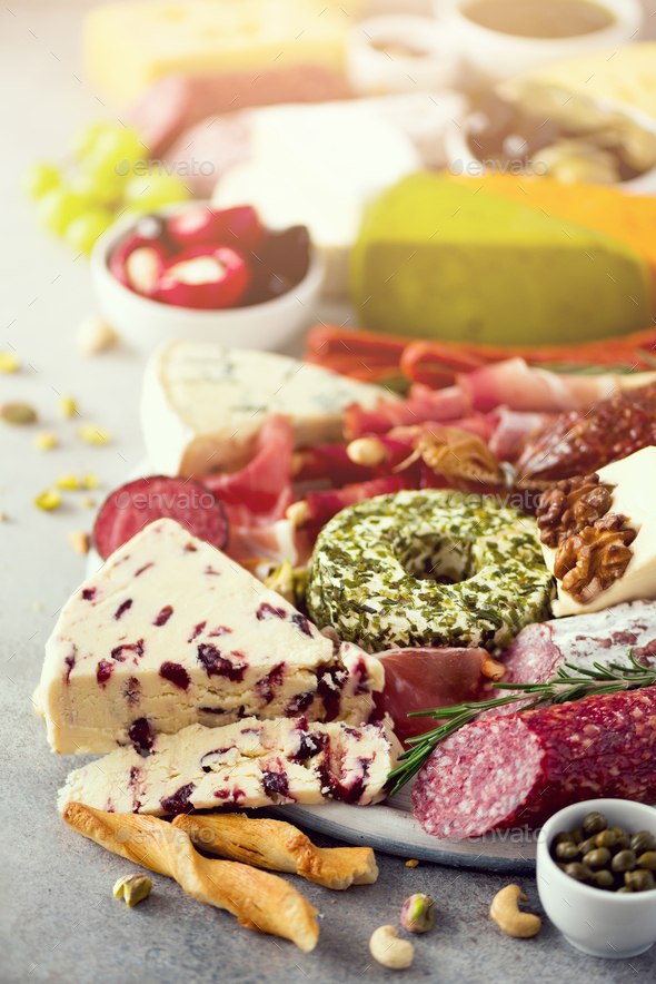 Cutting board with salami, cold smoked meat, prosciutto, ham, cheeses on grey background. Cheese and - Stock Photo - Images
