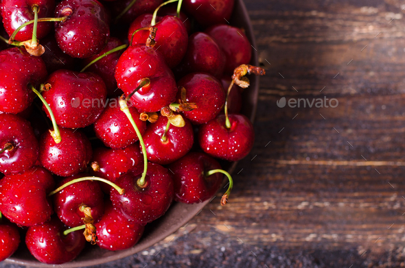 Fresh cherries in plate on dark wooden background with copy space. Summer and harvest concept - Stock Photo - Images