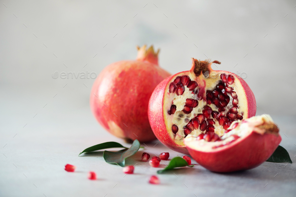 Ripe pomegranate fruit with green leaves on grey concrete background. Banner with copy space - Stock Photo - Images