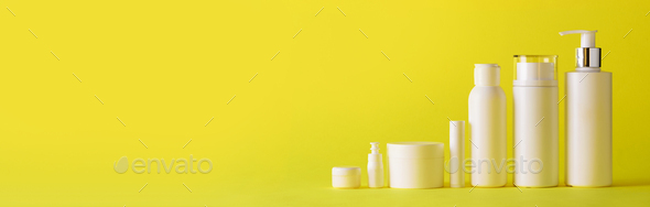 White cosmetic tubes on yellow background with copy space. Skin care, body treatment, beauty concept - Stock Photo - Images