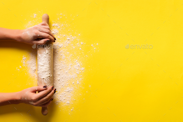 Girl hands keep rolling pin with flour on yellow background. Bake menu, recipe, homemade pastry - Stock Photo - Images