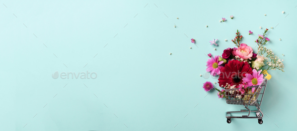 Shopping trolley with flowers on blue punchy pastel background. Banner with copy space. Top view - Stock Photo - Images