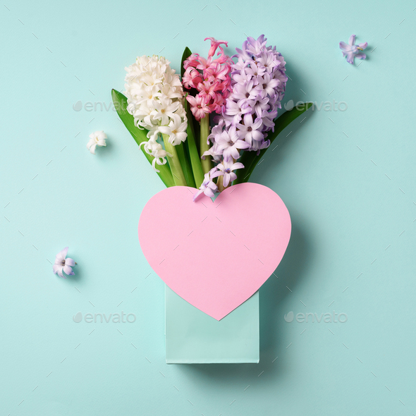Spring hyacinth flowers in shopping bag, pink paper heart on blue punchy pastel background. Square - Stock Photo - Images