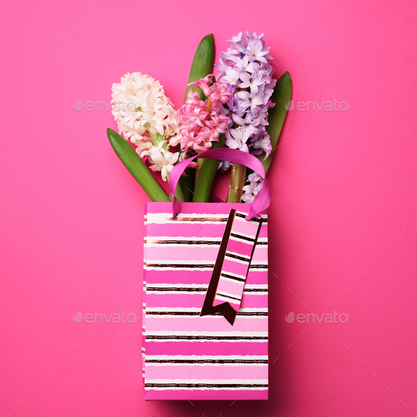 Spring hyacinth flowers in shopping paper bag on pink punchy pastel background. Banner with copy - Stock Photo - Images