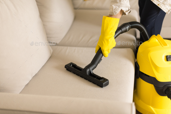 Woman cleaning sofa with yellow vacuum cleaner. Copy space. Clean concept - Stock Photo - Images