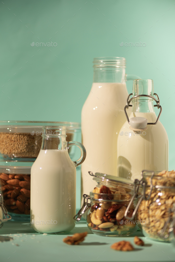 Vegan substitute dairy milk. Glass bottles with non-dairy milk and ingredients over blue background - Stock Photo - Images