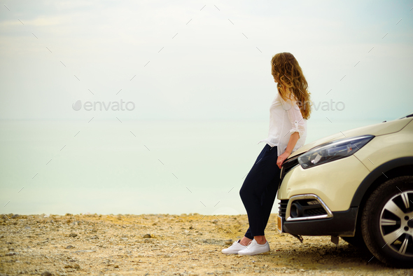 View of young woman traveler looking at sea sunset, sitting on hatchback car with the copy space - Stock Photo - Images