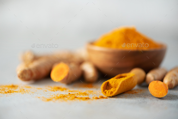 Turmeric powder in wooden bowl and fresh turmeric root on grey concrete background. Banner with copy - Stock Photo - Images