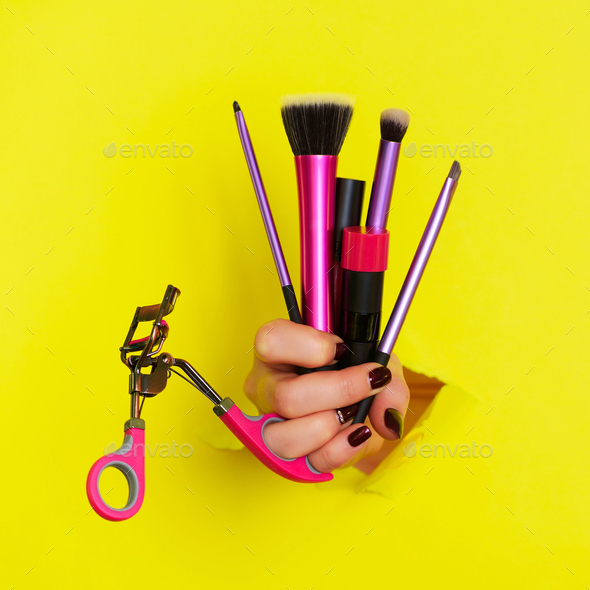 Woman hand with professional cosmetic tools for make up: brushes, mascara, lipstick, eyelash curler - Stock Photo - Images
