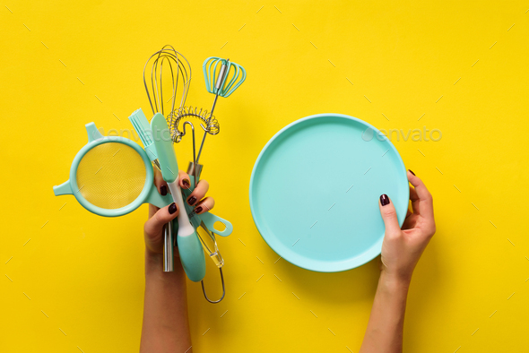 Woman hand holding kitchen utensils on yellow background. Baking tools - plate, brush, whisk - Stock Photo - Images