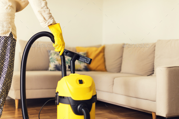 Woman cleaning sofa with yellow vacuum cleaner. Copy space. Cleaning service concept - Stock Photo - Images