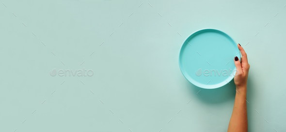 Female hand holding empty blue plate on pastel background with copy space. Healthy eating, diet - Stock Photo - Images