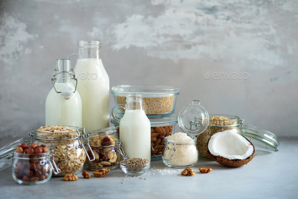 Glass bottles of vegan plant milk and almonds, nuts, coconut, hemp seed milk on grey concrete - Stock Photo - Images