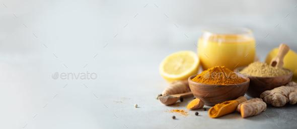 Healthy vegan turmeric latte or golden milk, turmeric root, ginger powder, black pepper over grey - Stock Photo - Images