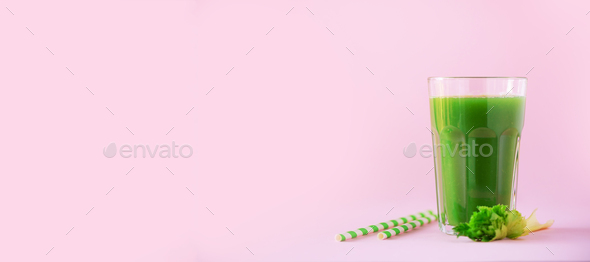 Glass of green celery smoothie on pink background. Banner with copy space. Fresh juice for detox - Stock Photo - Images